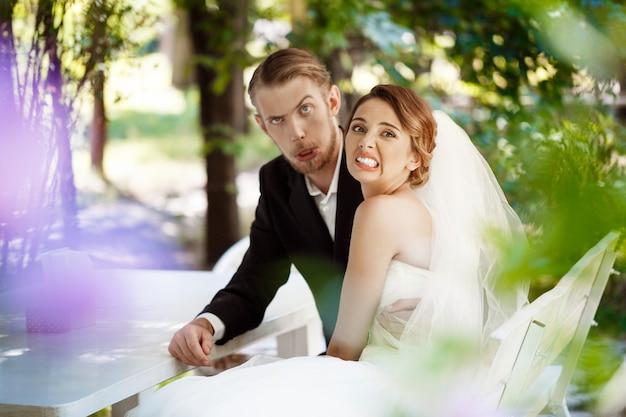 Giovani belle sposi che imbrogliano, sedendosi nel caffè all'aperto.