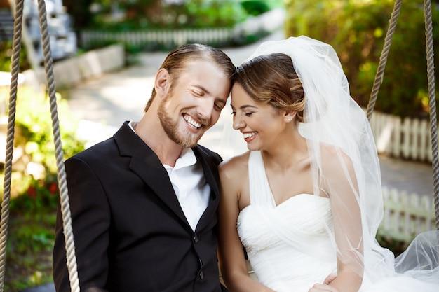Giovani belle sposi sorridenti, ridendo, seduto sull'altalena nel parco.