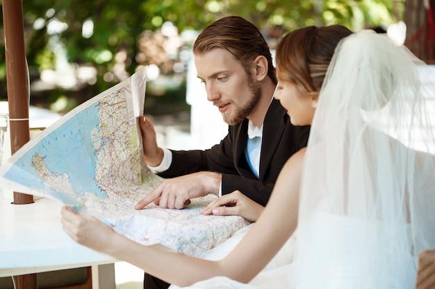 Giovani belle sposi sorridenti, scegliendo il viaggio di nozze, guardando la mappa.