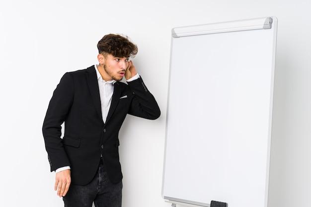 Giovani business coaching uomo arabo, cercando di ascoltare un gossip.