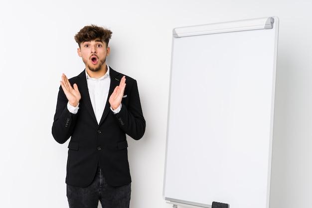 Giovani business coaching uomo arabo sorpreso e scioccato.