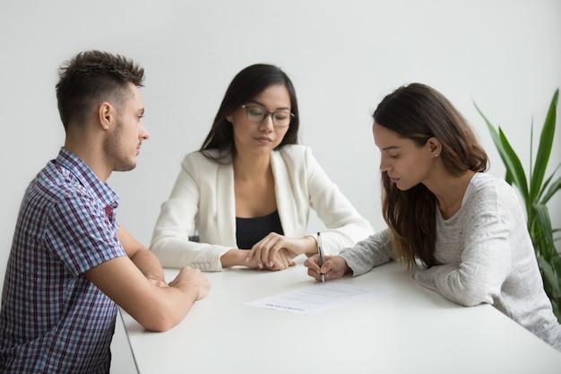 Giovani carte di divorzio del segno della moglie nell'ufficio dell'avvocato