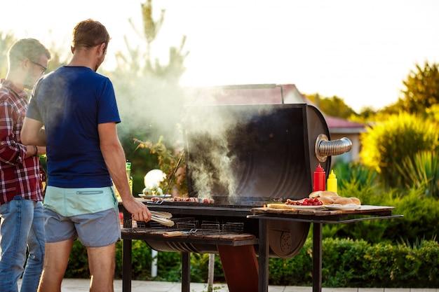 Giovani che arrostiscono barbecue sulla griglia nella campagna del cottage.