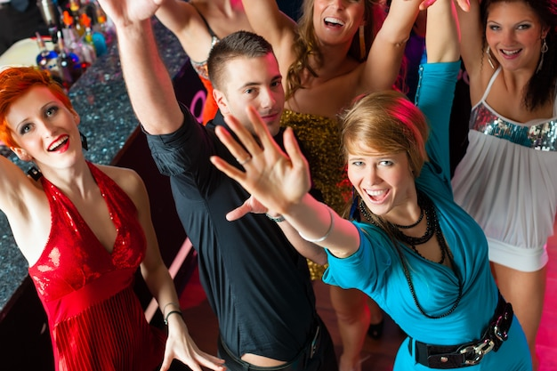 Giovani che ballano nel club o in discoteca, uomini e donne