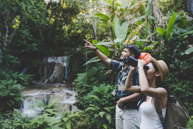 Giovani che camminano nella foresta con cascate. facendo un'escursione ad estate.