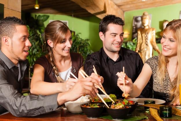 Giovani che mangiano nel ristorante tailandese