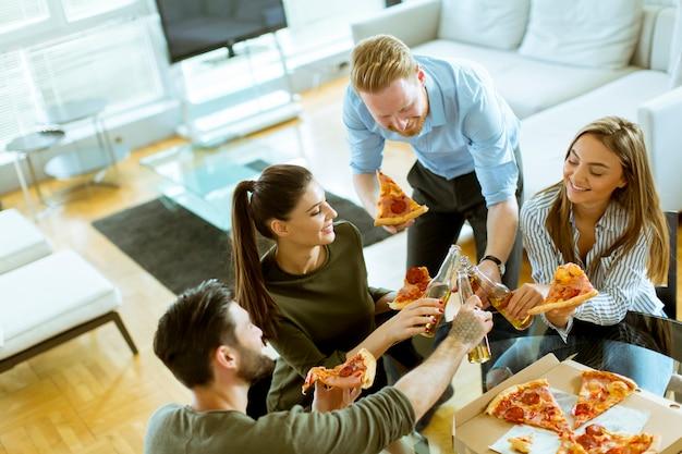 Giovani che mangiano pizza e bevono sidro negli interni moderni