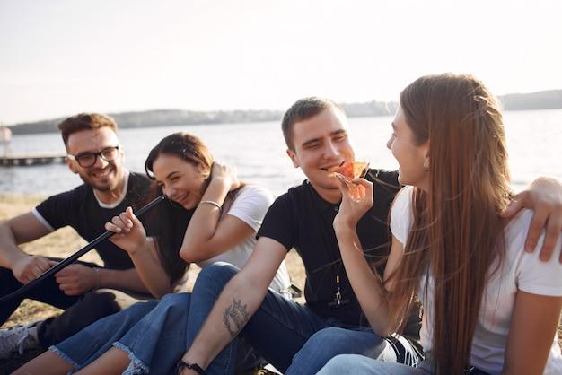 Giovani che mangiano pizza e che fumano shisha sulla spiaggia