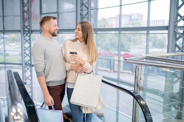 Giovani che ridono date che si guardano l'un l'altro mentre sono in piedi sulla scala mobile, godendosi lo shopping nel centro commerciale e parlando