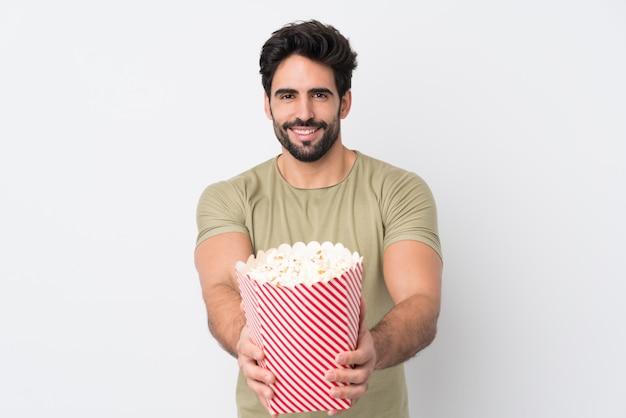 Giovani che tengono una grande ciotola di popcorn sopra la parete isolata