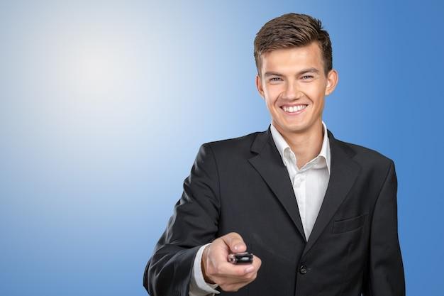 Giovani chiavi sorridenti della macchina della tenuta dell'uomo