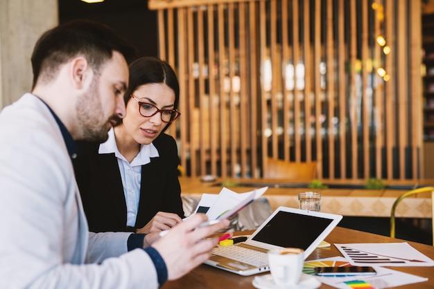 Giovani college d'affari che lavorano sodo seduti in una caffetteria dopo il lavoro e la scrittura di rapporti