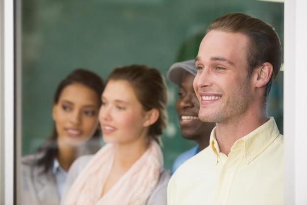Giovani colleghi felici che distolgono lo sguardo nell'ufficio