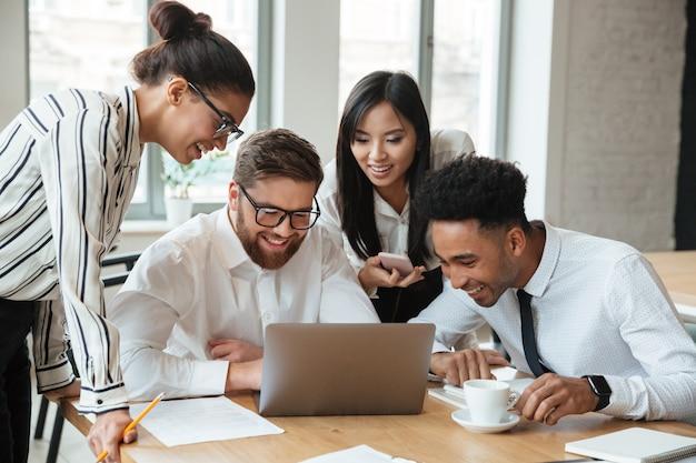 Giovani colleghi felici di affari che per mezzo del computer portatile.