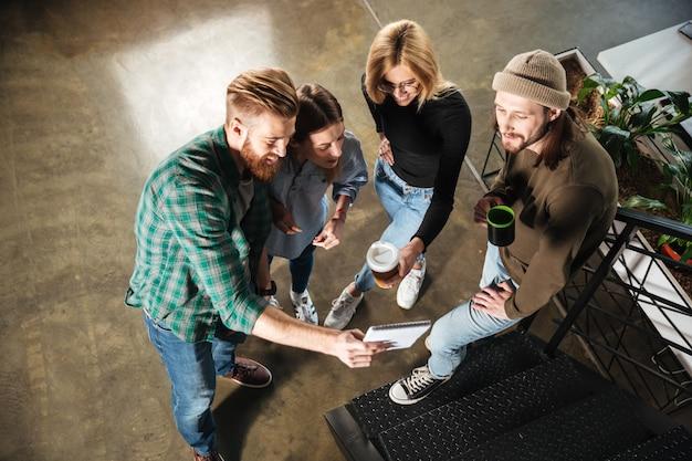 Giovani colleghi in ufficio a parlare tra loro azienda notebook