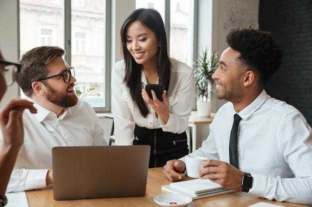 Giovani colleghi positivi cherful che per mezzo del computer portatile.