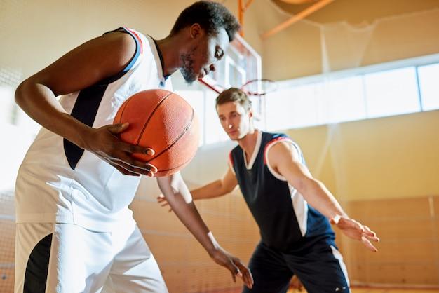 Giovani concorrenti che giocano a basket sul campo di allenamento