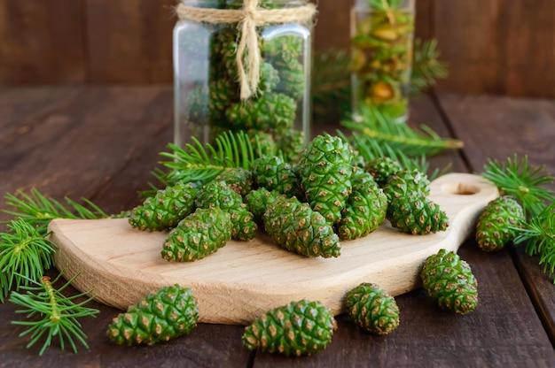 Giovani coni di abete verdi sulla tavola di legno. per fare l'infusione medicinale.