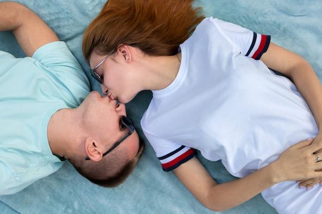 Giovani coppie adolescenti in occhiali da sole che si situano insieme sul panno blu che gode delle relazioni e del baciare di amore.