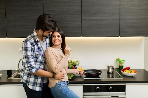 Giovani coppie adorabili che preparano pasto nella cucina mdoern