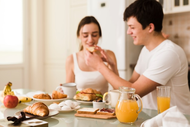 Giovani coppie adorabili che servono insieme prima colazione