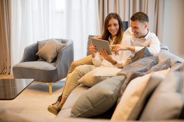 Giovani coppie adorabili con la compressa digitale nella stanza