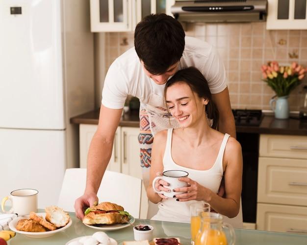 Giovani coppie adorabili insieme per la prima colazione