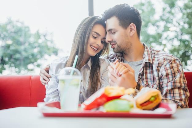 Giovani coppie adorabili nel fast food moderno che abbracciano insieme
