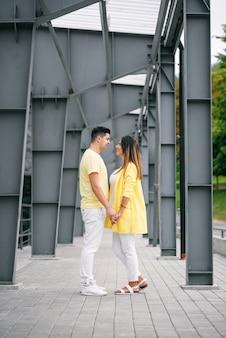 Giovani coppie adorabili nel tenersi per mano luminoso dei vestiti