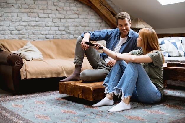 Giovani coppie adorabili sorridenti che si rilassano e che guardano tv a casa