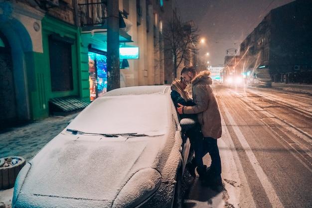 Giovani coppie adulte che si baciano sulla via innevata