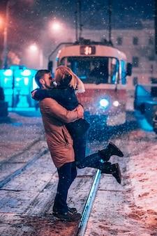 Giovani coppie adulte sulla linea del tram innevata