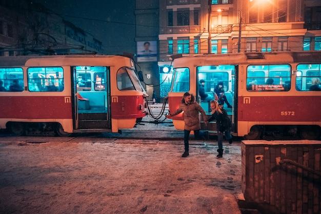 Giovani coppie adulte sulla stazione del tram innevata