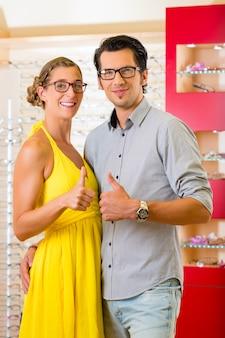 Giovani coppie all'ottico con gli occhiali
