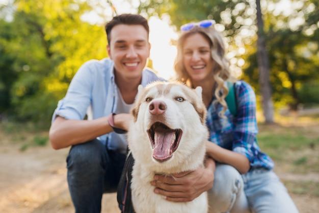 Giovani coppie alla moda che camminano con il cane in strada. uomo e donna felici insieme alla razza husky,