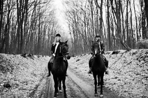 Giovani coppie alla moda che guidano sui cavalli alla foresta di autunno