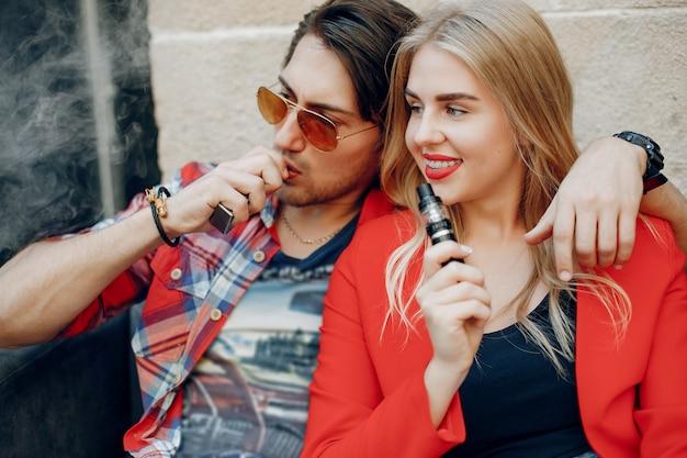 Giovani coppie alla moda con vape in un caffè