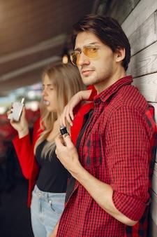 Giovani coppie alla moda con vape in una città