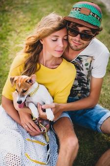 Giovani coppie alla moda hipster nell'amore che si siede sull'erba che gioca cane in spiaggia tropicale