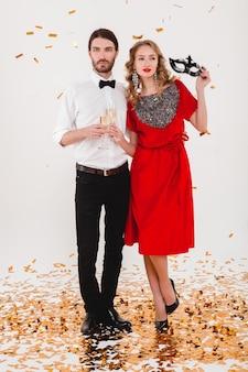Giovani coppie alla moda nell'amore che celebra il nuovo anno e beve champagne