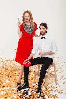 Giovani coppie alla moda nell'amore che tengono i vetri e bevono champagne, celebrando il nuovo anno
