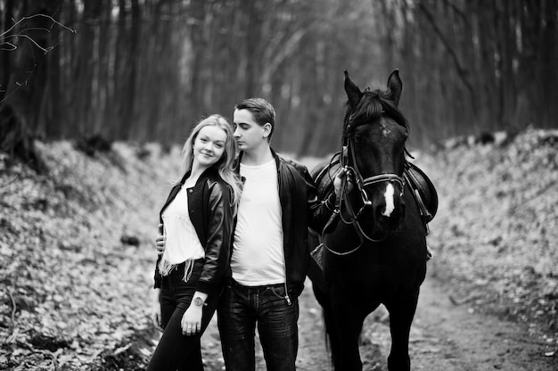 Giovani coppie alla moda nell'amore vicino al cavallo alla foresta di autunno