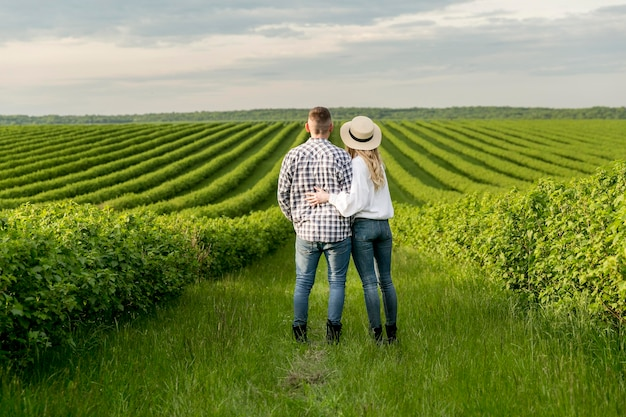 Giovani coppie alla vista ammirante dell'azienda agricola