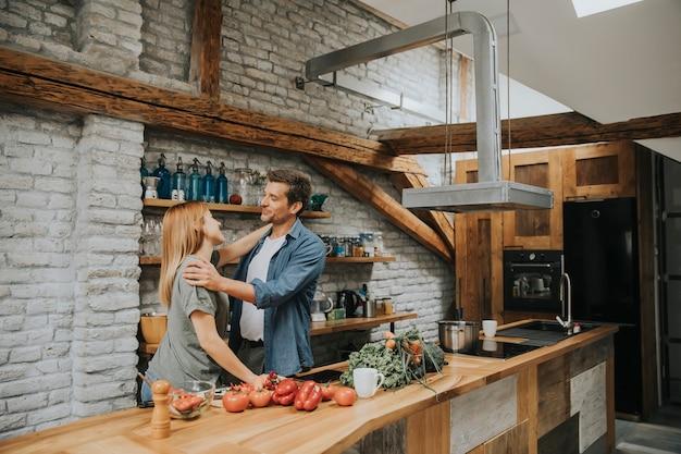 Giovani coppie allegre adorabili che cucinano insieme cena e si divertono alla cucina rustica