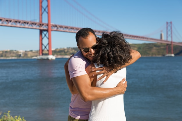 Giovani coppie allegre che abbracciano vicino al fiume