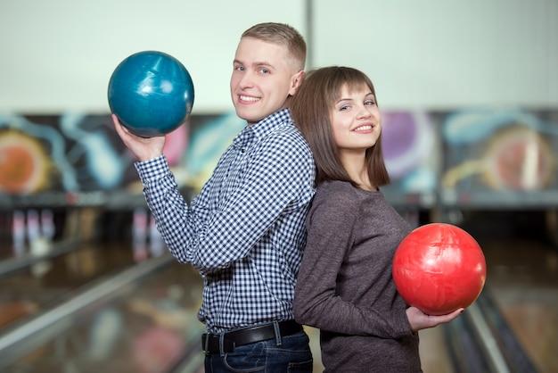 Giovani coppie allegre che giocano a bowling.