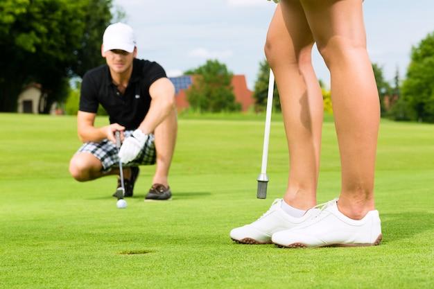 Giovani coppie allegre che giocano a golf su un corso