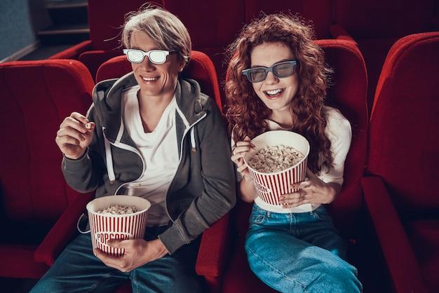 Giovani coppie allegre che guardano commedia nel cinema.