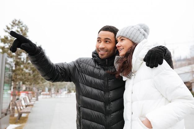 Giovani coppie allegre che indicano via al parco di inverno