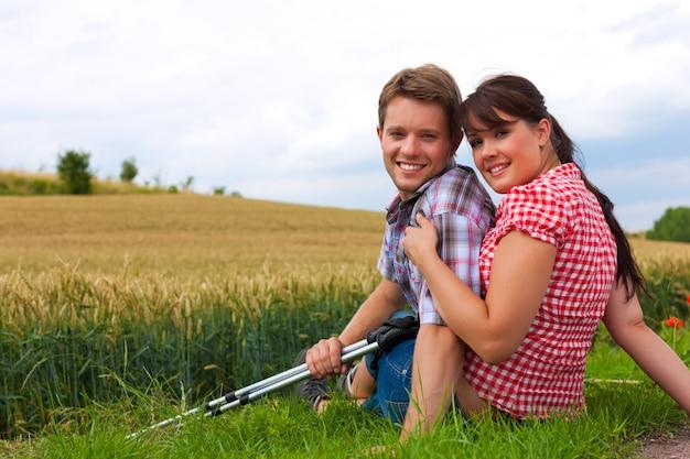 Giovani coppie allegre che posano con i bastoni d'escursione